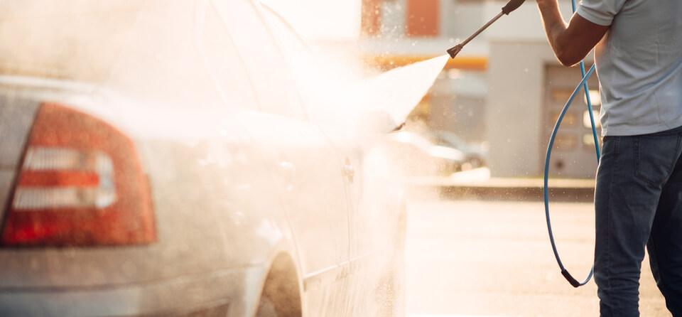Medewerker maakt auto schoon in wasstraat